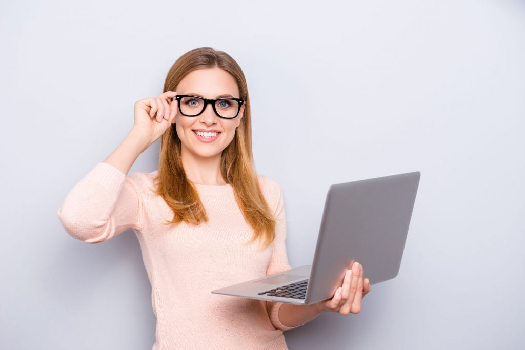 Close up portrait of confident smart intelligent clever attractive beautiful with beaming toothy shiny smile freelancer correcting eyewear holding laptop in hand isolated on gray background copy-space